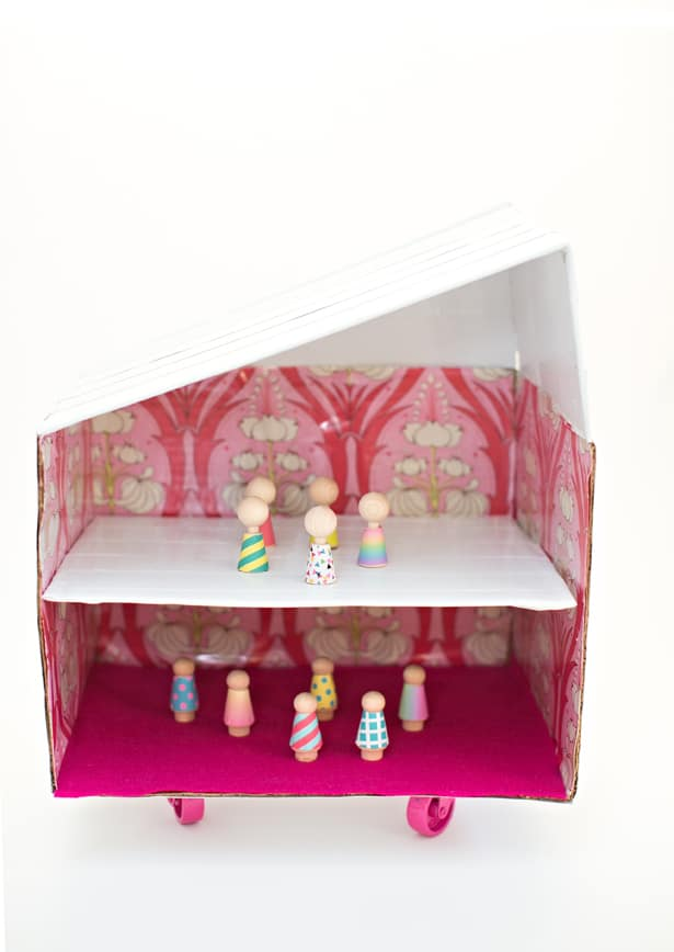 carboard box dollshouse with wheels and wallpapered walls